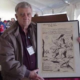 Jack Keller with an original page of Kid Colt art.